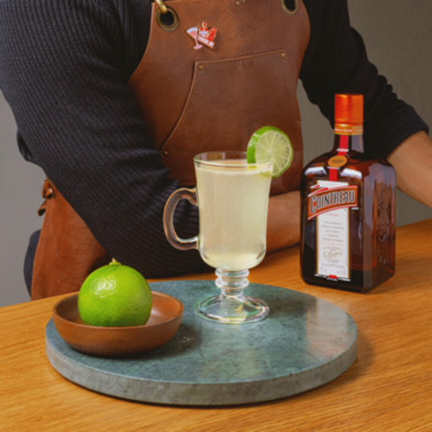 hot margarita with limes and cointreau bottle